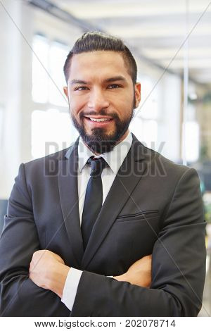 Successful and self confident businessman standing with arms crossed