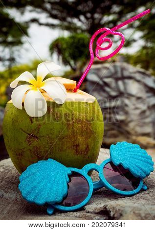 A fresh coconut with a red patterned straw and a fragrant plumeria flower stands on a stone, next to it there are sunglasses in the form of shells. vacation style
