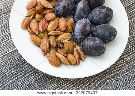 Black natural plums and seeds in plates, plums in white plates on wooden floor, Plum seeds