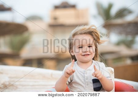 Child little boy with smiling happy cute face long blond hair hazel eyes in white shirt pointing with hands with pointer fingers at summer sunny day on vacations