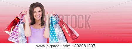 Digital composite of Shopper holding up bags against blurry red background