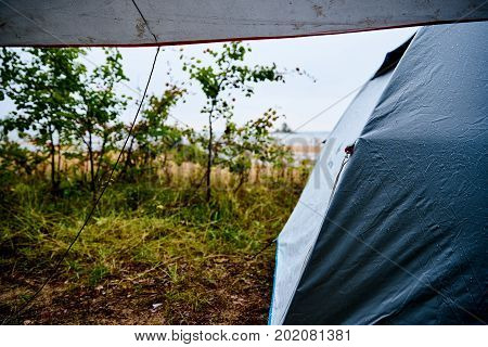 Camping at the beach during rain and bad weather in Sweden with a grey tent and tarp