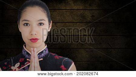 Digital composite of Close up of geisha hands together against dark grunge wood panel