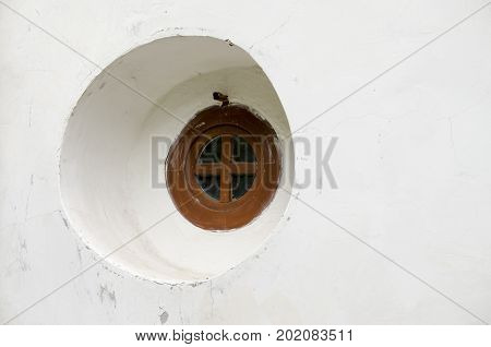 round, old window in the church in a white wall