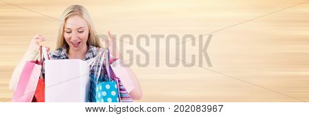 Digital composite of Shopper looking into bags against blurry cream background