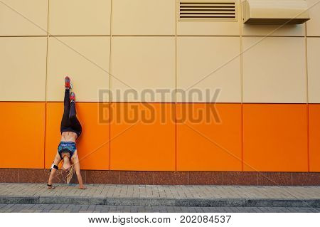 Sportive girl acrobat in a pose upside down on an orange background.