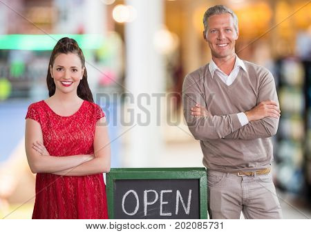 Digital composite of Business owners with open sign and arms folded against blurry background