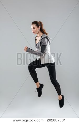 Vertical image of sports woman running over gray background