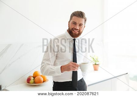 Smiling bearded business man drinking coffee on kitchen and looking at the camera