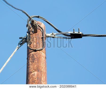 Power lines on a wooden pole with blue sky