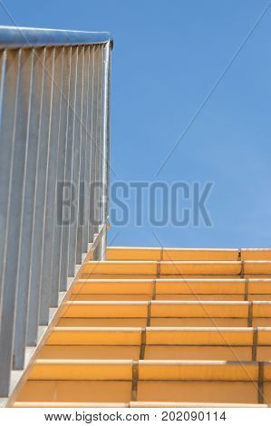 Stainless steel handrail and banister leading up outdoor tiled staircase