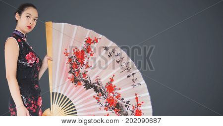 Digital composite of Geisha and giant fan against grey background