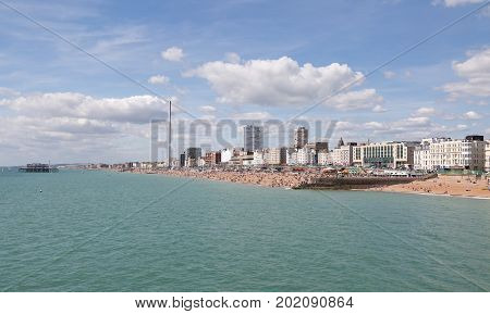 Brighton seafront and town with people enjoying the sunny beach