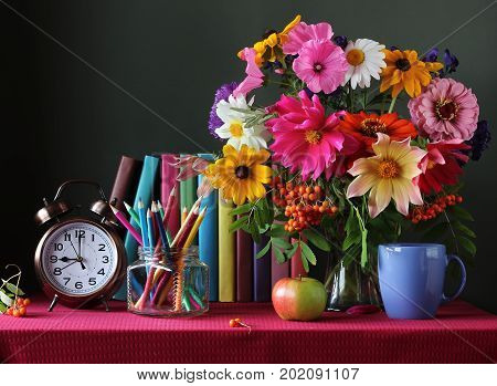 September 1 knowledge day. Back to school. Books alarm clock and a bouquet on the table. The teacher's day.
