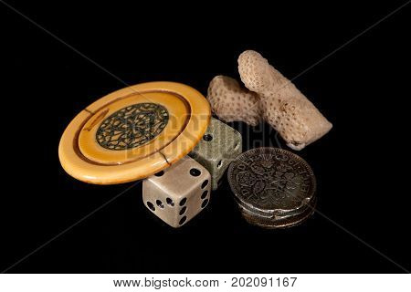 Vintage lucky charms. Antique poker chip dice squashed sixpences and coral. Collectable gambling tokens.