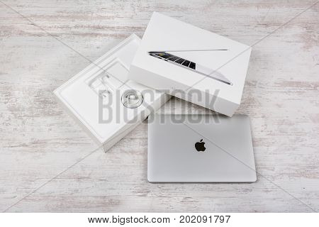 BURGAS, BULGARIA - AUGUST 10, 2017: MacBook Pro Retina Display with Touch bar and a Touch ID sensor integrated into the Power button, made by Apple Inc. on white wooden background.