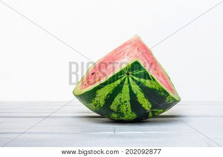 Slice of a watermelon on white wooden table on white background close-up. Minimalistic blank background