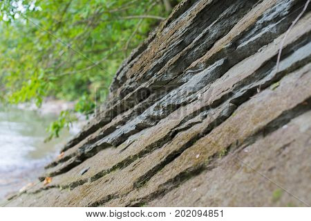 Layered Stone Rock Slope On The River Bank.