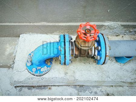 Outdoor main water shut-off valve system, compose of brass plumbing gate valve with red hand wheel and blue PVC pipes; installed on cement floor and in front of concrete wall.