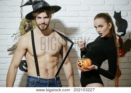 Halloween celebration and party. Man in witch hat with muscular torso. Girl pulling suspenders with pumpkin. Woman with blue lips in black body suit. Couple in love on white brick wall.