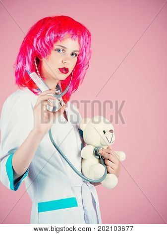 Girl curing teddy bear toy with syringe. Woman wearing medical uniform with stethoscope. Nurse in red wig on pink background. Doctor and patient. Health care and cure concept.