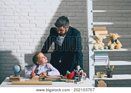 Family By Desk With School Supplies. Schoolgirl And Her Dad