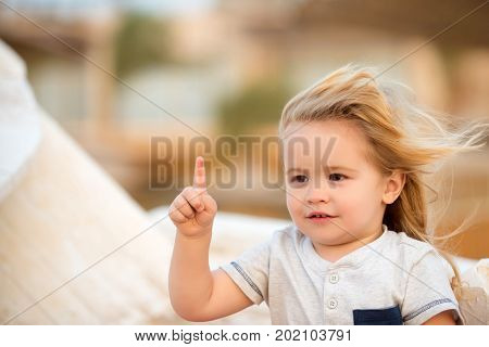 Kid little boy with smile on adorable face with blond long hair hazel eyes in white shirt posing with his pointer finger on sunny summer day