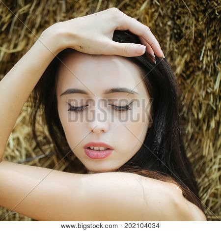 Girl with brunette hair posing in hay. Woman with closed eyes on cute face. Model with bare shoulders. Summer vacation concept. Leisure and relaxing on nature.