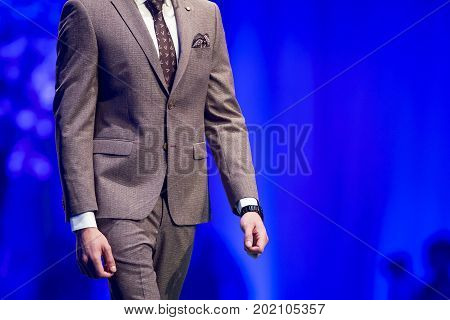 Sofia, Bulgaria - 22 March, 2017: A male model walks the runway in luxury business suit during a Fashion Show. Fashion catwalk event showing new collection of clothes. Blue background.