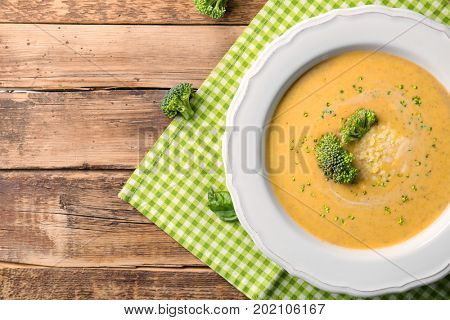 Broccoli cheddar soup in bowl on wooden kitchen table