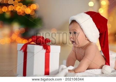 Cute little baby in Santa hat with gift box lying on floor against blurred Christmas lights