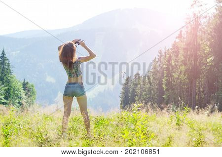 Young Woman Looks At The Mountains Through Binoculars, Outdoor Activities, Free Space.