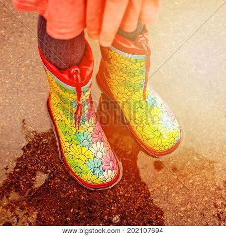 Little girs wearing rain boots is standing in a sunny puddle after rain. Walk and fun concept. Toned image. Space for text