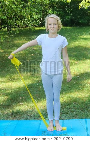 Beautiful school aged kid girl playing sports with a latex band and mat outdoors in the park
