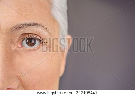 Closeup view of beautiful elderly woman on gray background