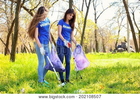 Young girls gathering garbage with trash pickers. Volunteering concept