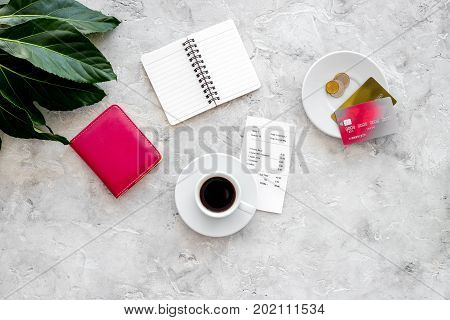 Pay restaurant bill. Bill, bank card, wallet, coins near cup of coffee on light stone table top view.
