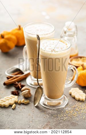 Pumpkin spice latte in tall mugs with cinnamon, nutmeg and cardamom