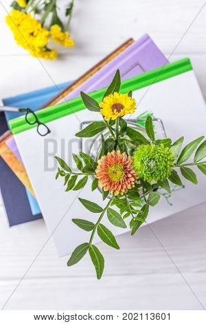 Hello, September. Hello, autumn. Books, bookmark glasses and chrysanthemum on a white wooden background. Top view