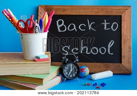 Back to school concept with stationery. School supplies on blue background. Frase Back to school written on blackboard. Schoolchild studies accessories with books clock and piece of chalk.