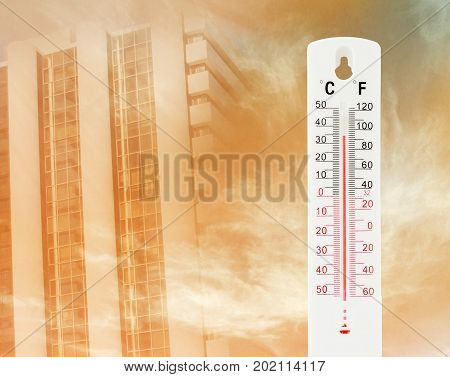 Tropical temperature of 34 degrees Celsius measured on an outdoor thermometer with tower background
