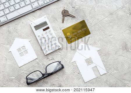 selling property online set with paper house on office desk stone background top view