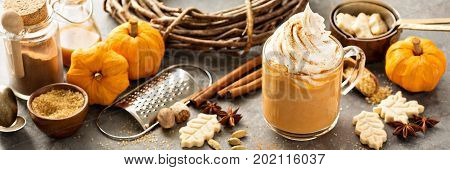 Pumpkin spice latte in a glass mug with cinnamon, nutmeg and cookies