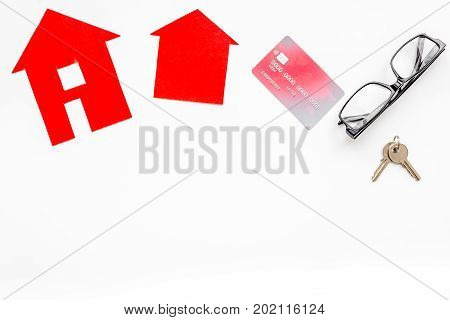 selling property online set with paper house on office desk white background top view mockup