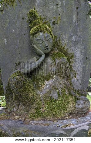 Tokyo, Japan - May 12, 2017: Bhudda statue in the garden of the Nezu museum covered with moss
