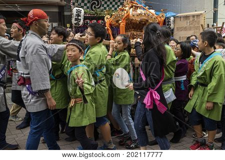 Tokyo, Japan - May 14, 2017: Children dressed in traditional kimono's carrying a Matsuri Shinto shrine at the Kanda Matsuri Festval