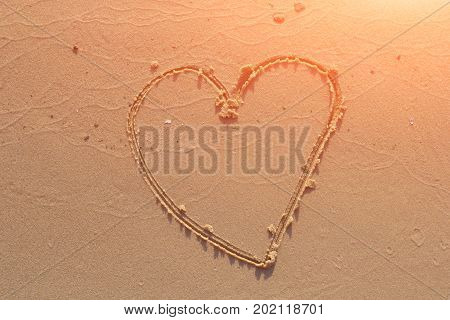 illustration of a heart drawn on sand.