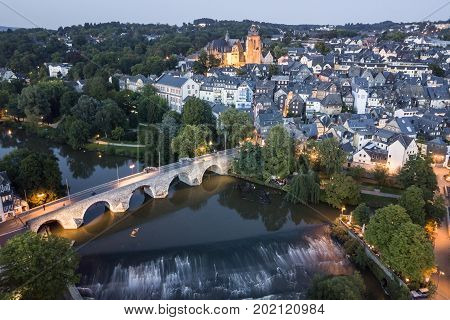 Ttown Wetzlar with the river Lahn and historic bridge illuminated at dusk. Hesse Germany