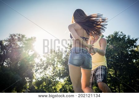 Mann turning woman dancing in the grass in summer park right before sunset