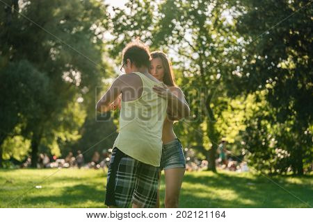 Mann turning woman while dancing Bachata in the sun right before sunset
